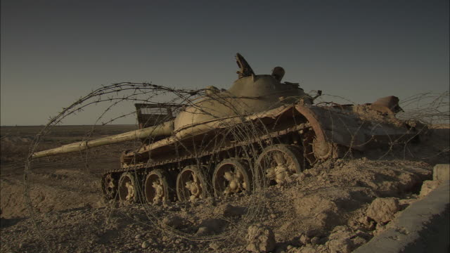 the hulk of a destroyed tank lies behind strands of concertina wire on the iran-iraq border. - iran stock videos & royalty-free footage