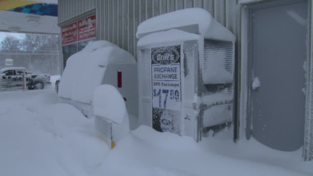 the ice machine and propane tank dispenser at a gas station in adams new york is covered in deep snow after a heavy lake effect snowstorm dumped... - scott mcpartland stock videos & royalty-free footage