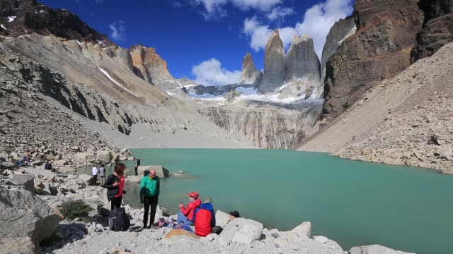 the iconic paine towers in torres del paine national park patagonia chile with tourists taking in the spectacle - turmspitze stock-videos und b-roll-filmmaterial