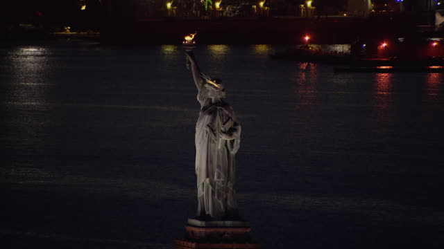 vídeos de stock, filmes e b-roll de the iconic statue of liberty overlooking the waters of new york harbor at night. - estátua