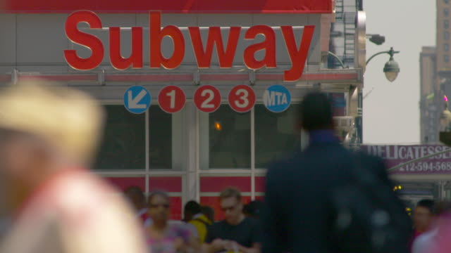 vídeos de stock, filmes e b-roll de cu of the iconic subway sign for the 1, 2,3 trains.  the streets are full of people walking underneath - passagem subterrânea via pública