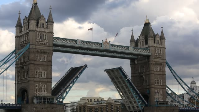 the iconic tower bridge spanning the river thames, opening to let a sailing boat down river, london, uk. - road closed sign stock videos & royalty-free footage