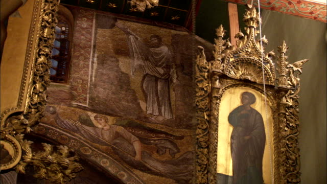 The iconostasis in the Basilica of Saint Catherine's Monastery shows a gilded image of Moses climbing Mount Sinai. Available in HD.
