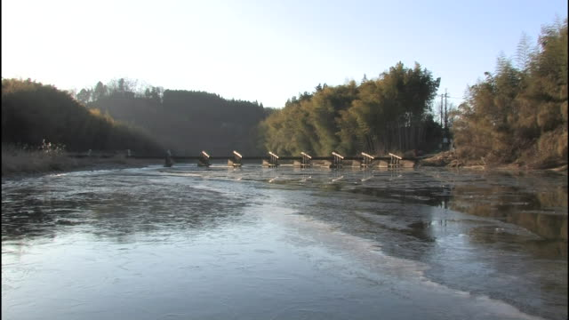 The icy Kuji River flows past wooded banks in Japan.