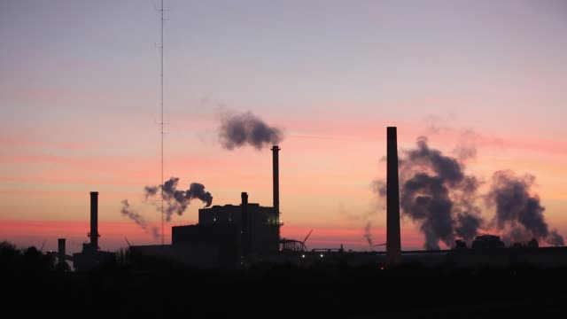 the iggesund paper board manufacturer in workington cumbria uk at sunset with wind turbines the plant is powered by a biofuel power station on site - smoke physical structure stock videos & royalty-free footage