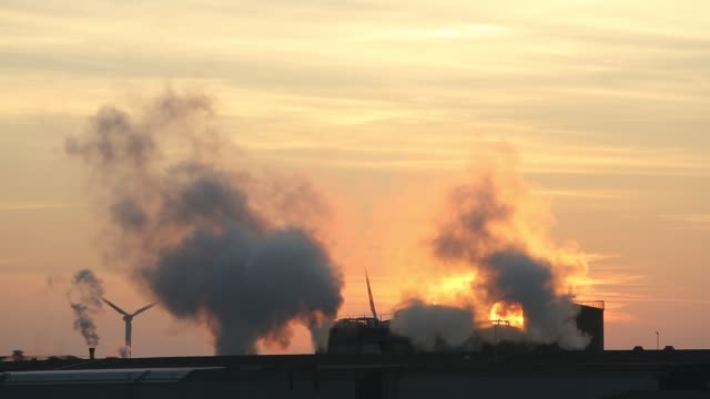 the iggesund paper board manufacturer in workington, cumbria, uk, at sunset, with wind turbines. the plant is powered by a biofuel power station, on... - chimney stock videos & royalty-free footage
