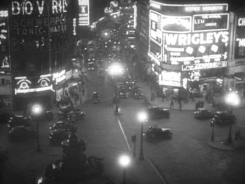 the illuminated advertising hoardings light up piccadilly circus. 1956. - ウェストエンド点の映像素材/bロール
