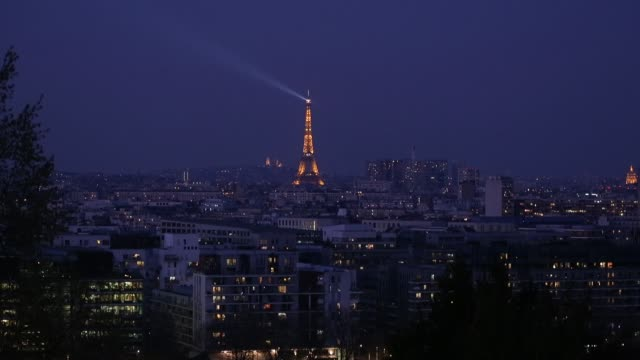 the illuminated eiffel tower and the paris buildings are seen at night while parisians remain confined to their homes during the coronavirus epidemic... - eiffel tower paris stock videos & royalty-free footage