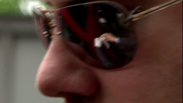 vídeos y material grabado en eventos de stock de the image of a detective putting on latex gloves reflects in his sunglasses. - detective