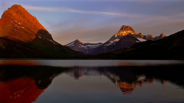 The image of a mountain reflects off Sherburne Lake.