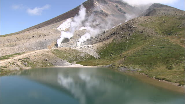 the image of mount asahi reflects on the surface of sugatami pond. - kamikawa subprefecture stock videos and b-roll footage