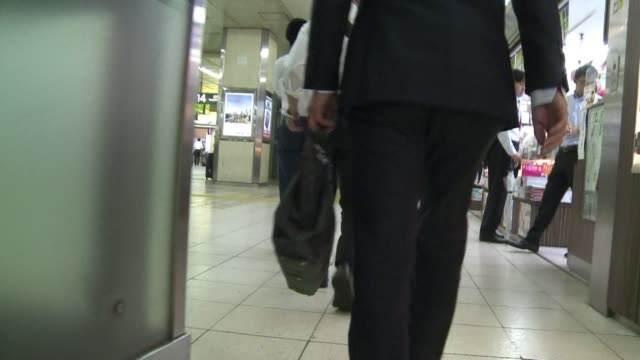 vídeos de stock, filmes e b-roll de the image of sozzled salarymen passed out on the streets ties knotted around heads has become so common in japans cities the clone like workaholics... - excesso de trabalho