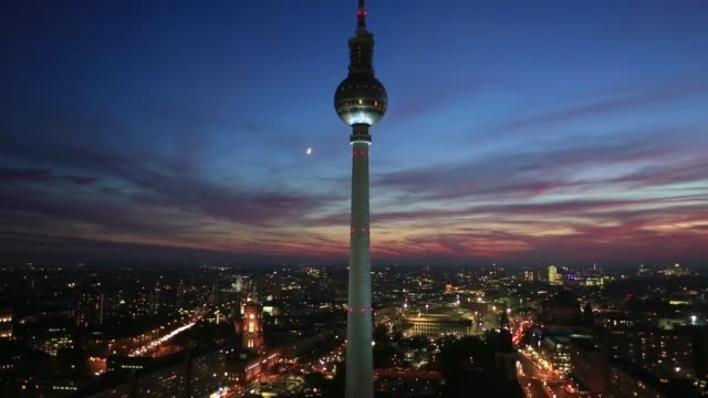 vídeos de stock, filmes e b-roll de the imposing fernsehturm berlin at dusk towering over the skyline of berlin germany on monday 27th october gvs of the tower at sunset and night - torre de televisão berlim