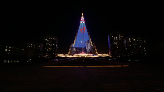 the infamous illuminated pyramid (ryugyong hotel) in pyongyang at night. time-lapse from ground level. north korea, drpk. - spoonfilm stock-videos und b-roll-filmmaterial