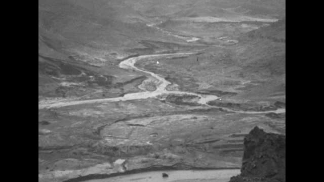the intact center segment of the collapsed st. francis dam, with an eroded stream and scoured valley; men with horses loaded with dead bodies - dam stock videos & royalty-free footage