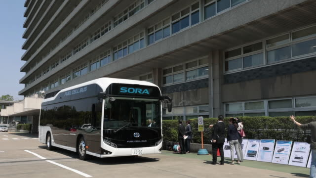 The interiors and exteriors of a Toyota Motor Corp Sora fuelcell bus the fuelcell bus travelling along a road and attendees onboard the fuelcell bus...