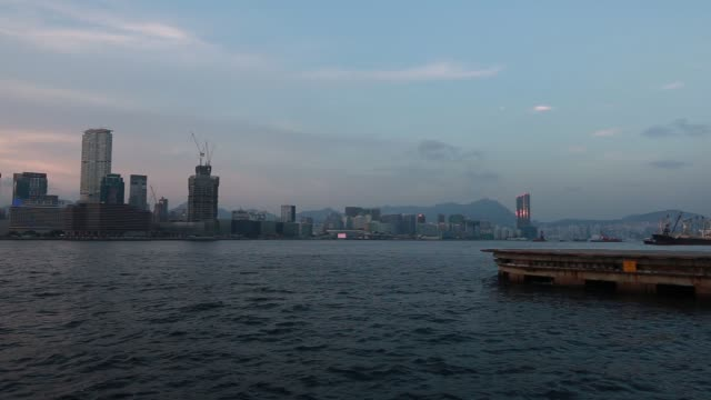 WS The International Commerce Centre center left and other commercial and residential buildings stand at dusk viewed from Victoria Harbor MS A ferry...