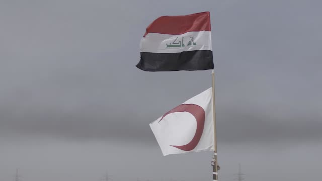 the iraqi flag and the medical red crescent flag above a iraiq military field hospital in mosul the military operation to liberate the city of mosul... - civilian stock videos & royalty-free footage