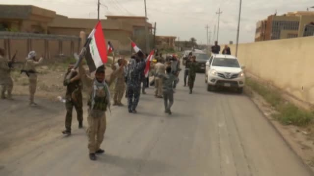 the iraqi security forces, backed by al-hashid al-shaabi, had seized control of tikrit from daesh on tuesday and they patrol in the city on april 2,... - isil konflikt stock-videos und b-roll-filmmaterial