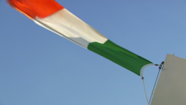 vídeos de stock, filmes e b-roll de the irish tricolour flag and british ensign fly side by side on a ferry crossing the irish sea. - um do lado do outro