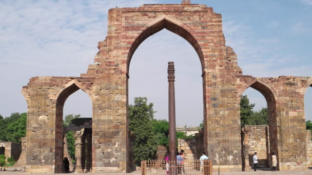 the iron pillar of delhi or ashoka column framed by the ruined arches of the qubbat-ul-islam mosque or dome of islam, later corrupted into quwwat-ul islam, in the world heritage city of qutb complex in new delhi - colonna architettonica video stock e b–roll