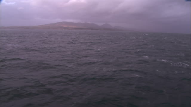 the isle of jura is seen across the ocean. - hebrides stock videos & royalty-free footage