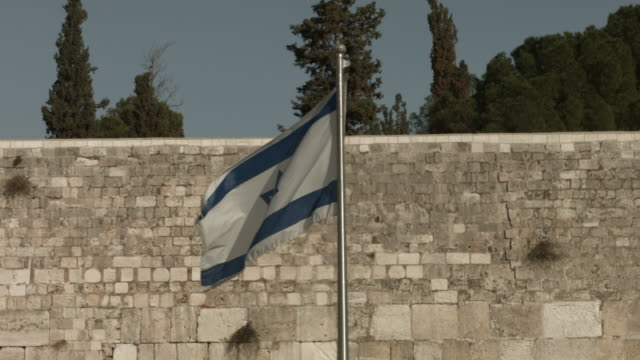 the israeli flag is viewed near the western wall in the the old city on november 25 2014 in jerusalem israel nine israelis have been killed in a... - jerusalem old city stock videos and b-roll footage
