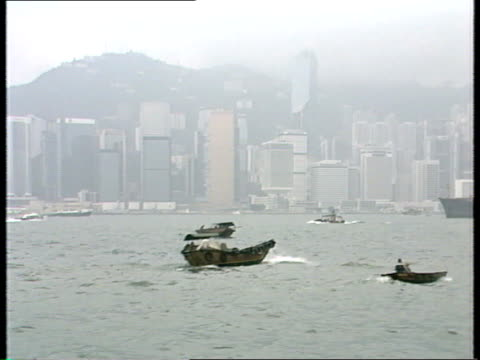 hong kong gvs / the ivory trade; hong kong: ships, junks and tugs in f/ground pass against backdrop of office blocks, incl soviet container ship... - dschunke stock-videos und b-roll-filmmaterial