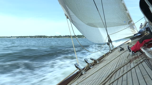 the j class yacht, velsheda, moves briskly through the water as the crew eases the sails to head downwind. - regatta stock-videos und b-roll-filmmaterial