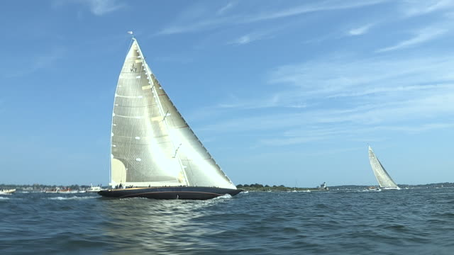 The J Class yachts Ranger and Velsheda sail upwind in close competition as they pass Rose Island.