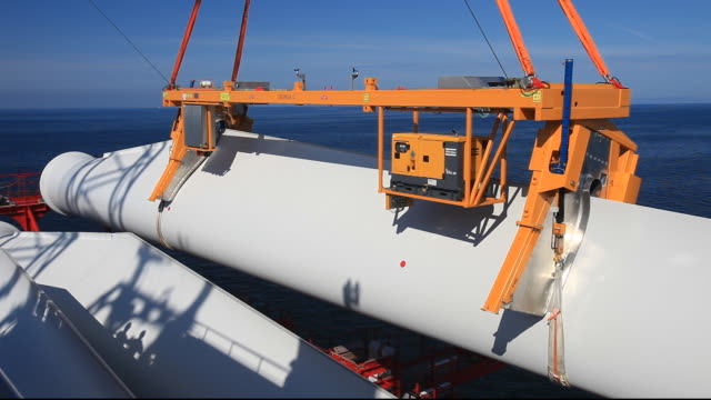 The jack up barge, Kraken, loaded with wind turbines for the Walney Offshore windfarm project, off Barrow in Furness, Cumbria, UK, lifts a turbine blade into place using a specialist cradle. When finished it will have 102, 3.6 MW turbines, giving a total c