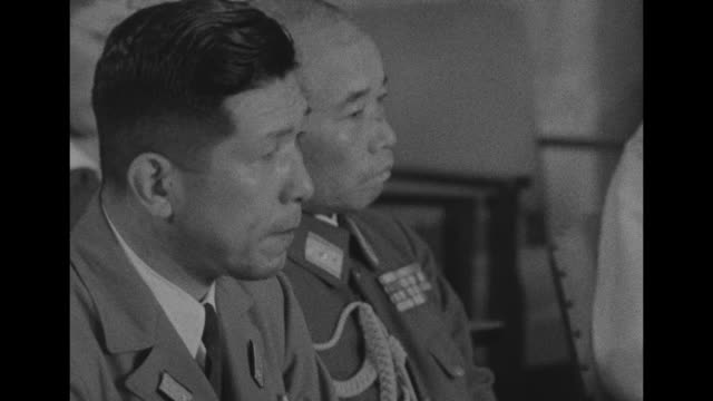 the japanese delegation takes their places at a conference table / closeup of vicechief of the army general staff torashiro kawabe and another / pan... - arrendersi video stock e b–roll