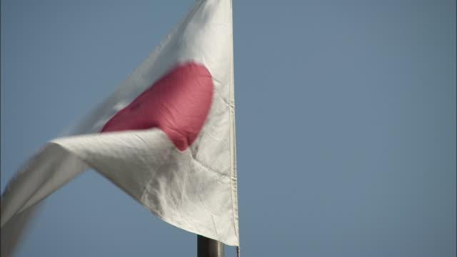 The Japanese flag flies from a flag pole.