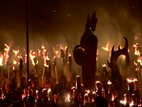 stockvideo's en b-roll-footage met the jarl or leader of the jarl squad is standing in a replica viking galley surrounded by flaming torches for the up helly aa festival - omgeven