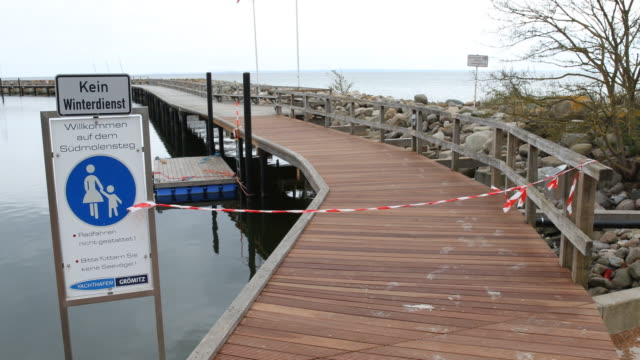 the jetty to the marina is closed during the novel coronavirus crisis on april 26, 2020 in groemitz, germany. while germany is taking first steps to... - deutsche nordseeregion stock-videos und b-roll-filmmaterial