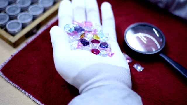 der juwelier hält diamanten in seinen händen. - schutzhandschuh stock-videos und b-roll-filmmaterial
