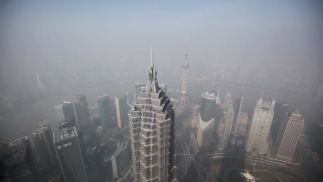the jin mao tower center left and the oriental pearl tower background center right stand among other commercial buildings seen from the shanghai... - jin mao tower stock videos & royalty-free footage