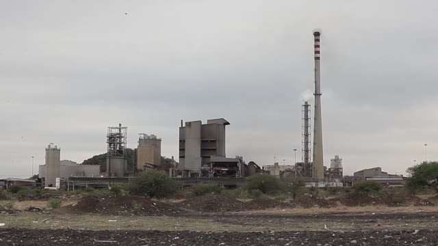 the karee mine shaft stands in the distance at the marikana mine operated by lonmin plc in marikana south africa on friday nov 6 workers walk past... - mine shaft stock videos and b-roll footage