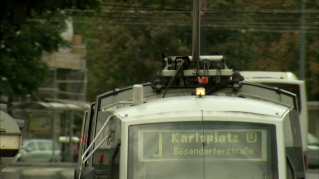 the karlsplatz tram passes pedestrians in vienna. available in hd. - カールスプラッツ点の映像素材/bロール