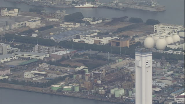 the keihin industrial zone lines the shores of the tsurumi river in kanagawa, japan. - yokohama stock videos and b-roll footage
