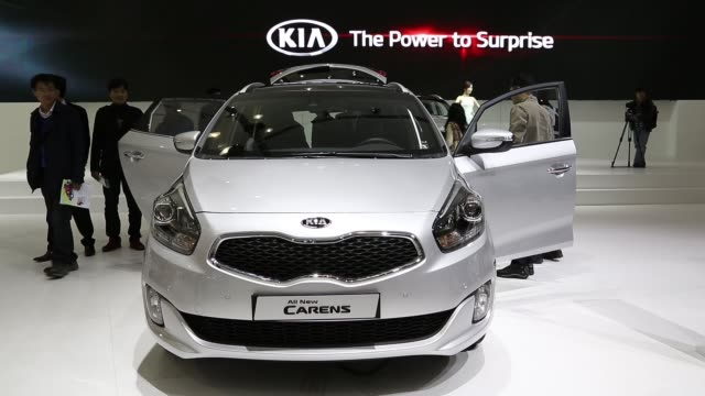 the kia motors corp carens car model stands on display during the press day of the seoul motor show in goyang an attendee sits at steering wheel of a... - goyang stock videos and b-roll footage