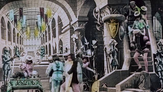 vídeos de stock e filmes b-roll de 1903 ws the king's court climbing up and down the stairs and arming themselves to rescue the kidnapped queen during the film illusions, le royaume des fées (the kingdom of fairies) by georges melies - colorido a mão