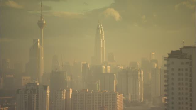 vídeos de stock, filmes e b-roll de the kl and petronas towers rise above other high-rises in kuala lumpur. - torre menara kuala lumpur