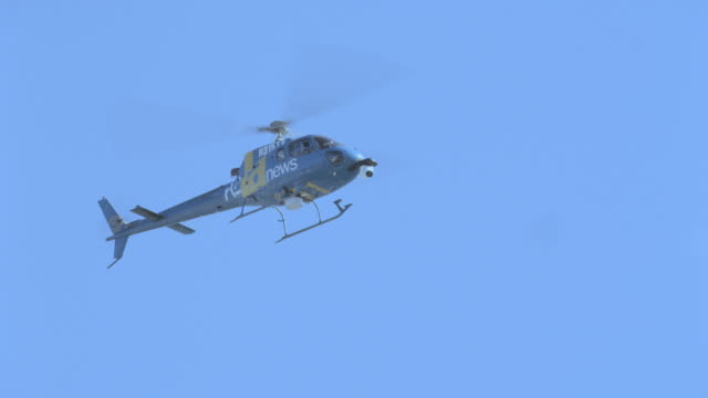 vídeos de stock e filmes b-roll de the ktla news helicopter hovers in a blue sky. - pairar