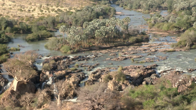 The Kunene River flows around rocks and islands leading to Epupa Falls.
