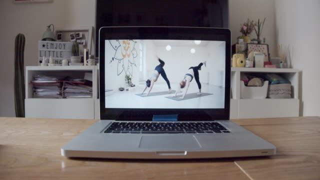 vídeos y material grabado en eventos de stock de el portátil está listo para una lección de video de yoga en línea - pilates
