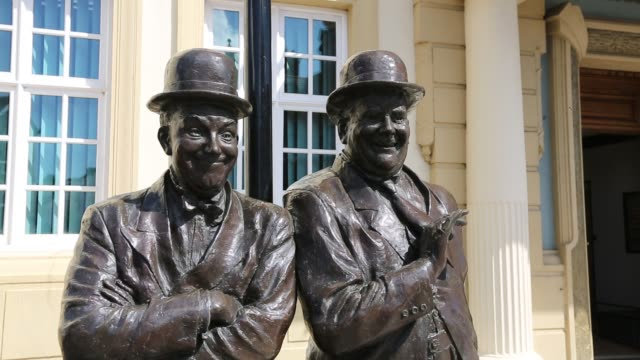the larel and hardy statue outside the coronation hall in ulverston, cumbria, uk. stan laurel was born in ulverston. the statue was designed and constructed by the artist graham ibbeson. - stan laurel stock videos & royalty-free footage