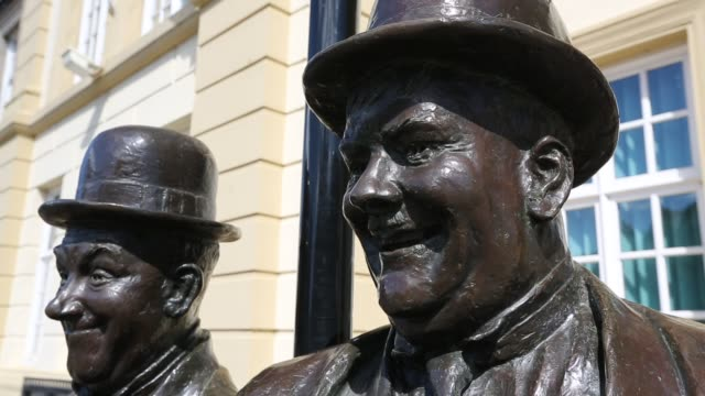 the larel and hardy statue outside the coronation hall in ulverston, cumbria, uk. stan laurel was born in ulverston. the statue was designed and constructed by the artist graham ibbeson. - oliver hardy stock videos & royalty-free footage