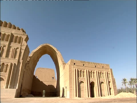 the large ancient archway of taq-e kisra casts a shadow over the stone wall behind it. - baghdad stock videos & royalty-free footage