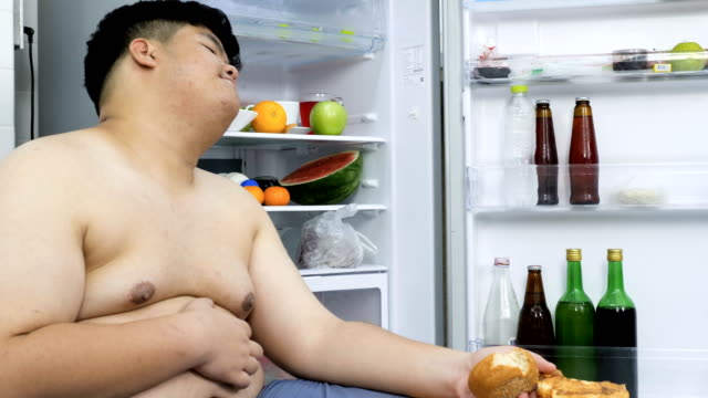 the large build man sleeps next to the fridge. - snack stock videos & royalty-free footage